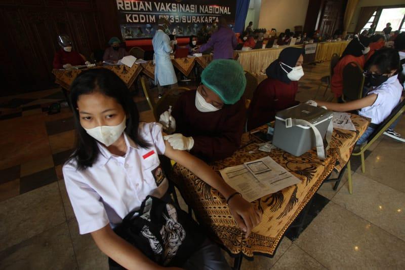 Petugas medis menyuntikkan vaksin kepada pelajar saat vaksinasi Covid-19 di Graha Saba Buana, Sumber, Banjarsari, Solo, Rabu (22/9/2021). Menurut data Dinas Pendidikan (Disdik) Kota Solo sebanyak 55.925 pelajar dari total 73.000 pelajar atau sekitar 77% pelajar di Kota Solo sudah mengikuti vaksinasi Covid-19. Sehingga target vaksinasi Covid-19 khusus pelajar optimistis selesai akhir September 2021. (Espos/Nicolous Irawan)
